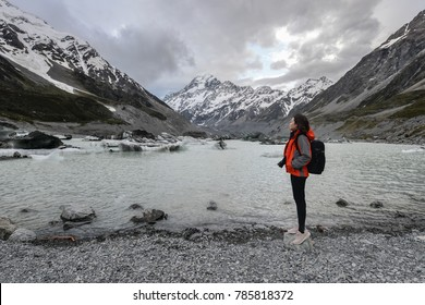 Woman backpacker and photographer standing on the destination point at Mt Cook in New Zealand
