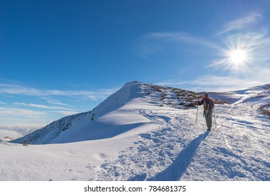 Woman backpacker trekking on snow on the Alps. Rear view, winter lifestyle, cold feeling, sun star in backlight.