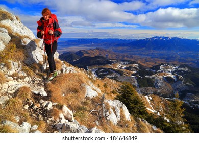 Woman backpacker walking a mountain trail in sunny day
