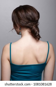 Woman from backside on gray background. Female with dark hair and white clean perfect skin