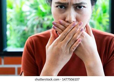 Woman with bad breath covering mouth, halitosis concept