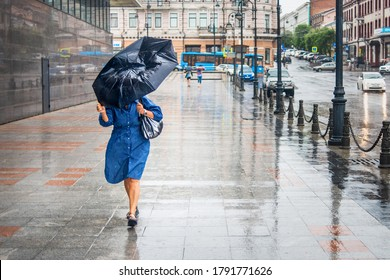 Woman in bad rainy weather walks down the street and tries to keep the umbrella from the strong wind. City landscape in rainy weather. City scenes in the rain.