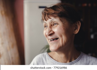 A woman with bad teeth smiles happily. Problem with teeth, no teeth, a blank for the tooth bridge
