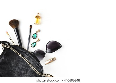 Woman bag on the white table, makeup accessories and jewerly with perfume. Female white mock-up background. Flat lay