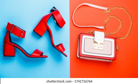 Woman bag, sandals on red and blue background isolation. Ladies bag and stylish red shoes. Stylish red women's leather sandals shoes. Summery sandals for a woman. High heel women shoes and a bags.