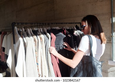 Woman with bag in sunglasses choosing clothes on racks in boutique.