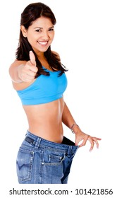 Woman in baggy pants with thumbs up - isolated over a white background