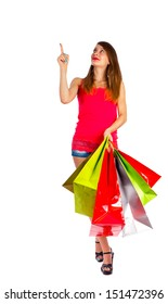 Woman with bags pointing upwards a blank space.
