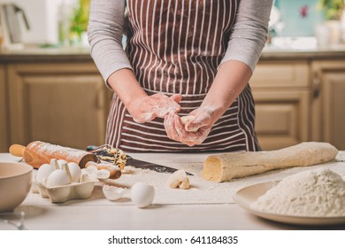 Woman bake pies. Confectioner makes desserts. Making buns. Dough on the table. Knead the dough.