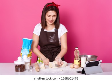 Woman baker cuts dough in small parts, ready for sculpting hot cross buns, make pies from dough, wears brown apron, casual white t shirt, red hair band, posing isolated over pink background.
