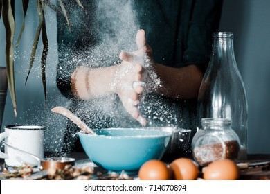 woman baker sprinkled flour on dough, cooking pasta by chef in kitchen on dark background. process of preparing pizza or bread with chefs hands.