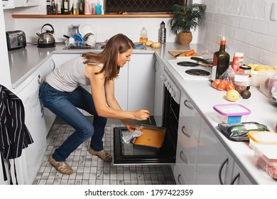 A woman is baking cake in a kitchen oven, checking if it is ready with a wooden stick