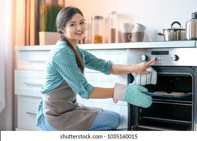 Woman baking cookies in oven indoors