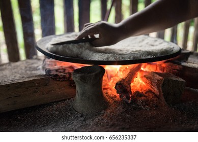 woman baking yuca bread over the fire