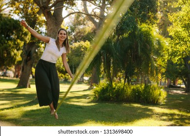 Woman balancing her walk on a loose rope tied between two trees. Woman practicing slack rope walking in a park.