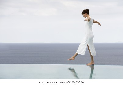 A woman balancing on the edge of a pool
