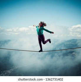 Woman balancing on a rope above clouds and mountains , while listening music . The concept of freedom.