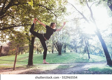 Woman balancing a tightrope or slackline outdoor in a city park in autumn - slacklining, balance, training concept - colorful filtered