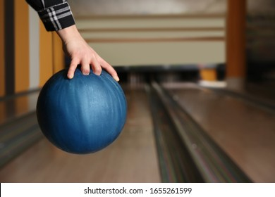 Woman with ball in bowling club, closeup. Space for text