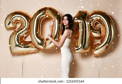 Woman With Balloons Celebrating At Party. Portrait Of Beautiful Smiling Happy  excited Laughing Girl In Shiny  Dress Under Snow Confetti Having Fun With Gold 2019 Balloons On beige nude Background