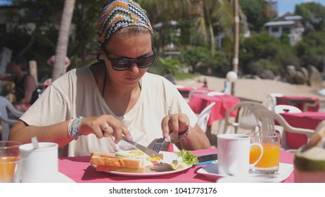 Woman in bandana and sunglasses spreads bread toasts with Butter in Beach Restaurant at the Sea. Tasty American breakfast near the sea at Coral Cove beach, Koh Samui, Thailand.