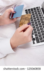 Woman banking or shopping online holding her credit card ready to enter the details on her computer keyboard