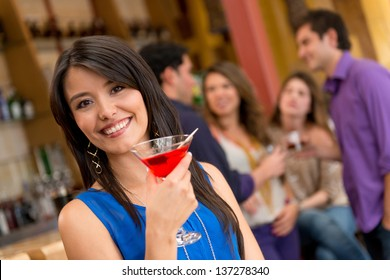 Woman at the bar having a drink and looking happy