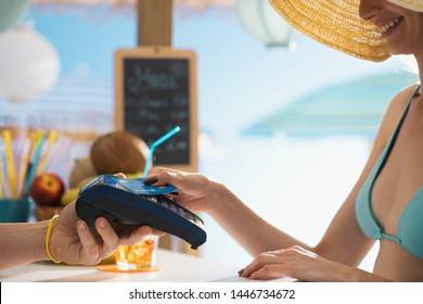 Woman at the bar paying using a contactless credit card, she is leaning it on the POS teminal, payments and technology concept