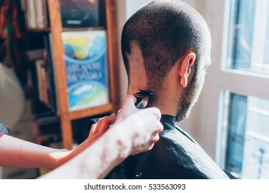 Woman barber cutting hair using razor - beauty, hair style concept