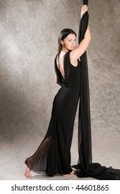 Woman with bare feet in an evening dress in black.