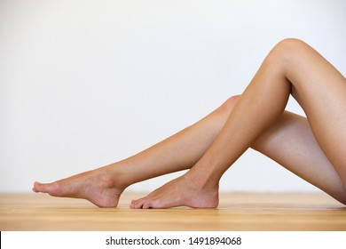 Woman bare feet on the floor. Legs care and skin treatment concept.