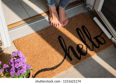 woman in bare feet standing at front door or new home with welcome mat