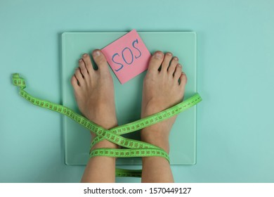 Woman with bare feet wrapped in measuring tape measures her weight on scale against blue background. Slimming concept. Top view