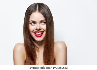 Woman with bare shoulders Laughs and looks away lipstick background