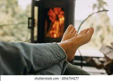 Woman barefoot relaxing in comfortable home, cozy warm moments. Feet on background of modern black fireplace and big windows with view on mountains.