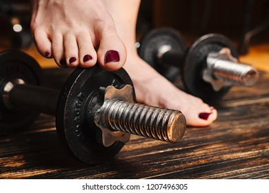 Woman barefoot standing with one feet on a dumbbell, surrounded with workout equipment