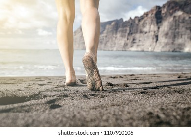 Woman barefoot walking on a beach, summer inspiration. Female naked legs running, walking or jogging on sand at seaside and ocean, inspirational landscape, Tenerife Canary Islands, Spain.