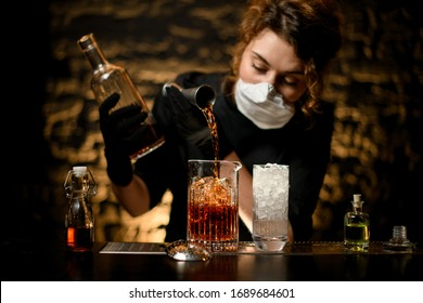 woman bartender in black clothes pours alcoholic into large glass with ice. White medical mask on her face and black gloves on hands for protection from coronavirus.