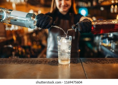 Woman bartender mixing alcoholic coctail in pub
