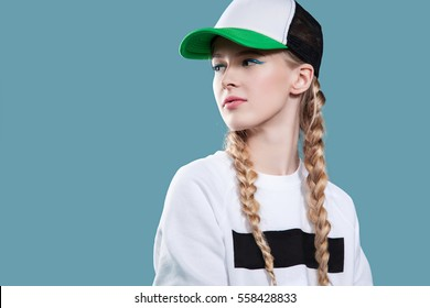 893b58d6258dd Woman in a baseball cap and a white sweatshirt is on a blue background