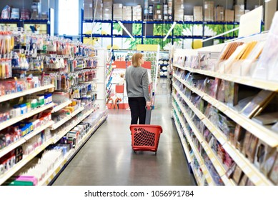 Woman with a basket on wheels in a commercial hypermarket