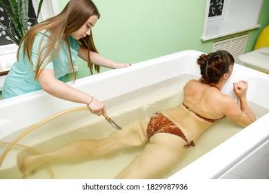 Woman in bath during hydromassage in beauty spa salon. Underwater hydrotherapy massage procedure
