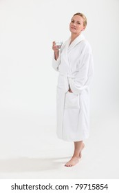 Woman in bath robe with a glass of water