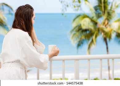 Woman in bath robe looking at beautiful ocean view  from a tropical balcony with morning coffee.