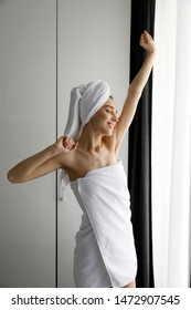 Woman in bath towel stretching hands near the window in morning