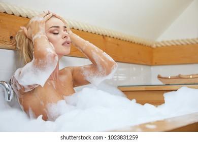 Woman bathes in a bathtub with foam