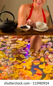 Woman bathing in spa with color therapy, the bathtub is lit with colorful lights, lots of flower petals on tub and tea