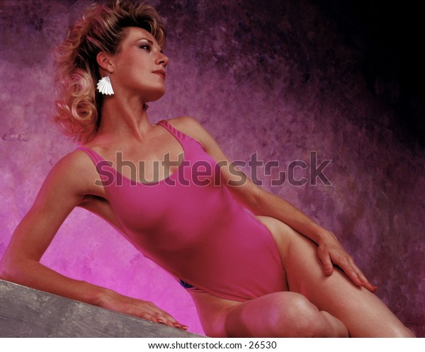 Woman in bathing suit leaning on her arm.