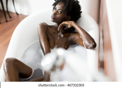 Woman bathing in a tub full of foam