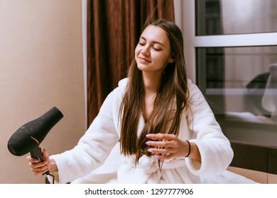 a woman in a bathrobe dries her hair with a hairdryer e14df16ff